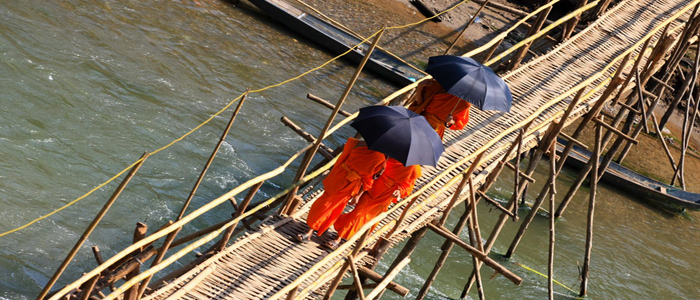Monks crossing bamboo bridge Lao